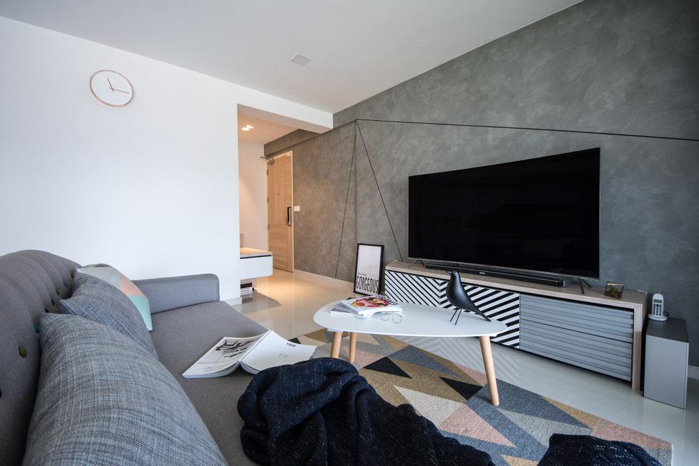 Телевизор на тумбе вдоль стены с серыми обоями
