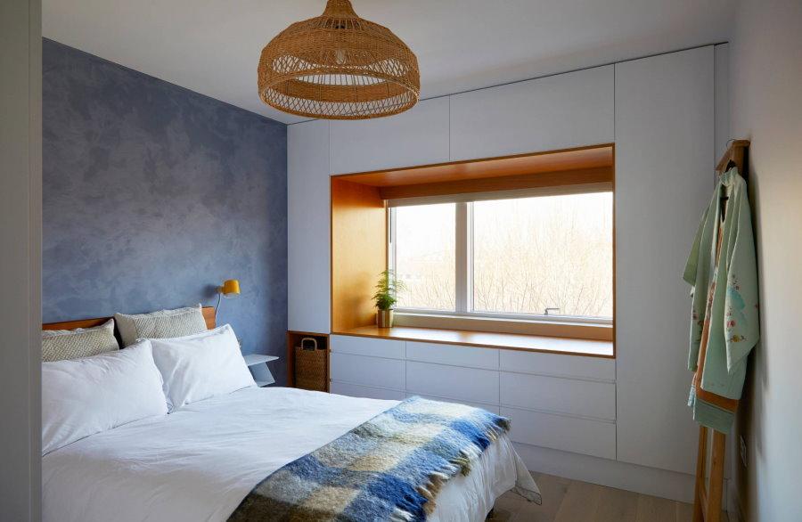Встроенная мебель вокруг окна в небольшой комнате