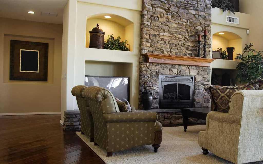 Удобные кресла перед фальш-камином в гостиной