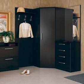 Черный шкаф в углу комнаты