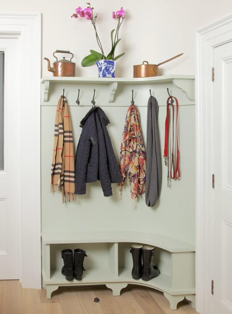 Куртки и шарфы на угловой вешалке в коридоре